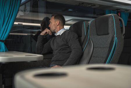 Comfortable Luxury Coach Bus Travel. Caucasian Men in His 40s on the International Journey Inside Bus. Transportation Theme. Stock fotó