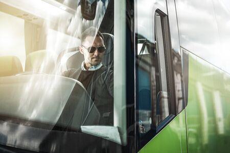 Caucasian Bus Driver Behind the Wheel of Modern Vehicle. Coach Bus Driving Theme. Public Transportation Concept. Stock fotó