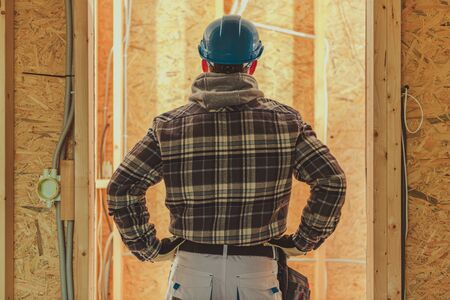 Caucasian Contractor Worker in His 40s Wearing White Hard Hat in Front of Newly Built House Interior.