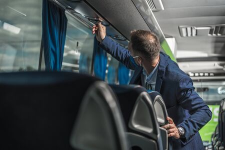 Public Coach Bus Driver With Protective Face Mask On Checking Air Fan Above Passenger Seats.  Stock fotó