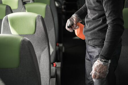 Male Cleaning Crew Worker With Spray Bottle In Hand Sanitizing Interior Of Intercity Coach Bus.