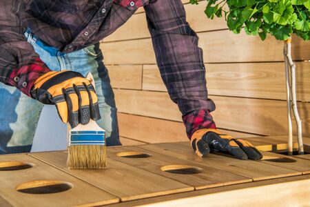 Handyman Applying Coat Of Oil Finish Onto Surface Of Outdoor Wood Furniture. Stock fotó