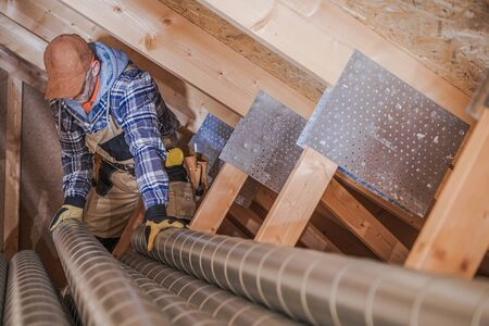 Male Ventilation Technician Installing New Air Vent System In Attic Of Residential Building.
