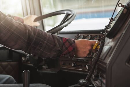 Semi Truck Male Driver Inside Of Vehicle Behind Steering Wheel. Transportation Industry Concept.