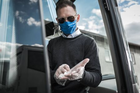 Caucasian Coach Bus Driver With Protective Face Mask Putting On Gloves And Getting Ready For Work During Pandemic. Stock fotó