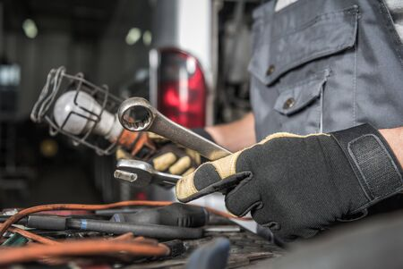 Male Auto Mechanic Picking Correct Tools To Fix Coach Bus In Vehicle Repair Shop.