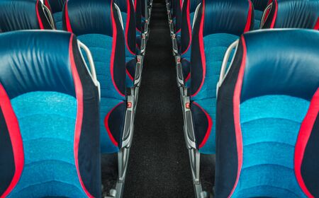 Image Of Empty Travel Bus Interior With Rows Of Blue And Red Fabric Seats And Long Corridor.