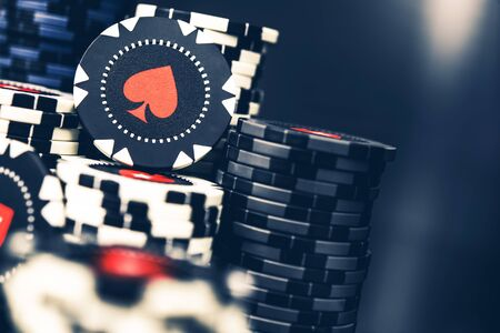 Tall Pile Of Black And White Casino Poker Chips With Red Spade Symbol.