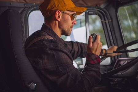 Caucasian Male Truck Driver Communicating On Two Way Radio Inside Of Vehicle Cab.  Stock fotó