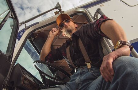 Professional Male Trucker In Cabin Of Parked Vehicle Relaxing And Looking Out At Rest Stop. Stock fotó