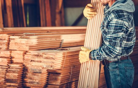 Male Worker Picking Up Bundle Of Lumber From Stack Of Wooden Planks At Building Material Warehouse.