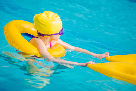Swimming Pool Theme. Caucasian Girl Learning How To Swim with Support Accessories. Stock fotó