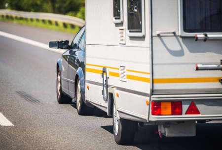 Transportation and Recreation Theme. Summer Vacation with Small Travel Trailer. Compact Car Pulling Small Trailer.