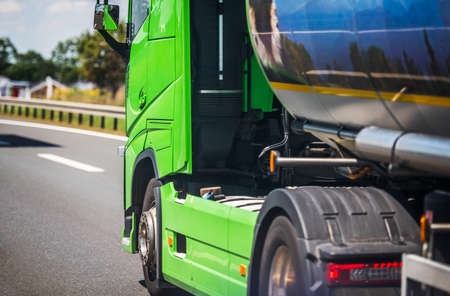 Bright Green Chemical Liquids Semi Truck on Highway. Dangerous Products Transportation Theme.