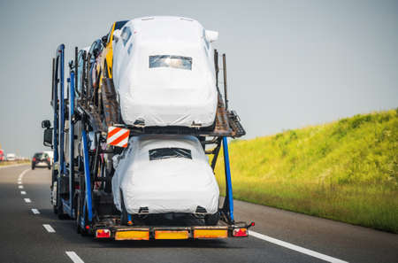 Car Carrier Trailer Full of Vehicles Driving Down the Highway. Car Hauler Semi Truck Vehicle Transportation.