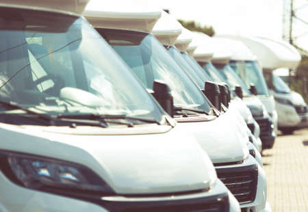 Line of Brand New Camper Vans Motorhomes Awaiting Clients on Dealership Sales Lot. Recreational Vehicles Selling. Caravaning Industry.