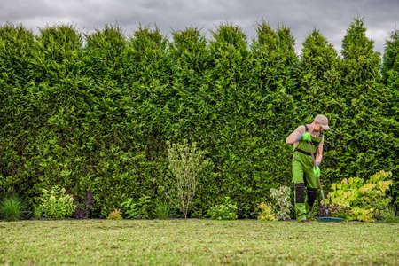 Caucasian Gardener in His 40s Raking Freshly Mowed Grass From the Backyard Garden Lawn. Landscaping Theme. Zdjęcie Seryjne
