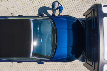 Caucasian Towing Truck Driver and Modern Repossessed Convertible Car Moving Back to Bank Owner. Repossession and Car Loans Theme. Aerial View.