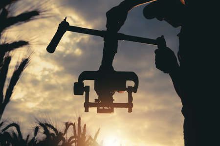Professional Handheld Video Camera Stabilizator in Use. Taking Documentary Shot During Scenic Sunset Between Rye Field. DSLR Video Production Pro Equipment. Imagens