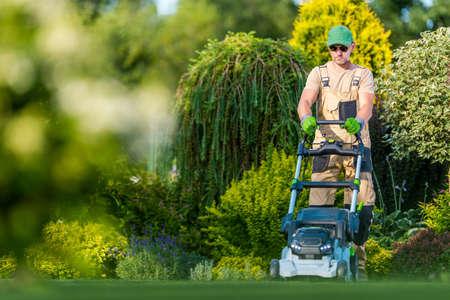 Beautiful Garden Backyard Grass Mowing by Caucasian Men in His 40s. Gardener and His Modern Mowing Equipment. Landscaping Theme.