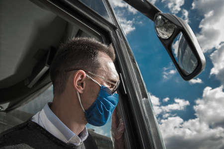Caucasian Shuttle Bus Driver in His 40s Wearing Face Mask During Pandemic. Public Transportation Industry.