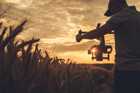 Cinema and Stock Footage Production. Caucasian Video Camera Operator in His 40s with Gimbal Stabilization Taking Steady Scenic Sunset Shot Between Rye Field.