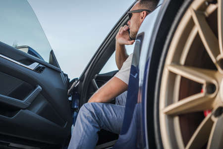 Caucasian Men in His 40s Making Phone Call While Seating in His Exotic Car. Transportation and Automotive Theme. Road Assistance Call. Imagens
