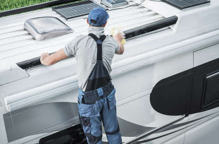 Recreational Vehicles Industry Theme. Caucasian RV Service Worker Washing Camper Van Roof Using Large Soft Sponge and Cleaning Detergent.