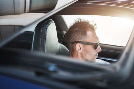 Caucasian Driver in His 40s Driving with Sunroof Opened During Hot Summer Day.