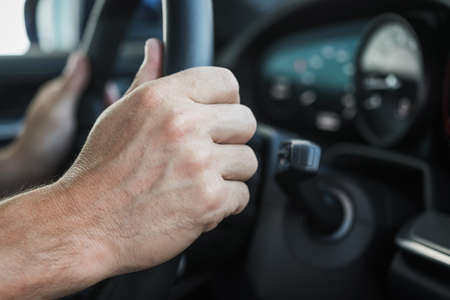 Male Driver Holding On To Steering Wheel Of Car And Operating Vehicle Close Up. Standard-Bild