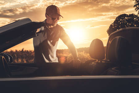 Caucasian Driver in His 40s and Convertible Car Summer Road Trip. Scenic Countryside Sunset. Transportation and Automotive Theme. Stock Photo