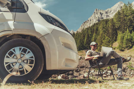 Caucasian Men with Modern Laptop Computer in His Hands Working Remotely While Camping in RV Camper Van Motorhome. High Mountains Landscape in a Background. Work and Travel Theme. Mont Blanc Massif Italy.