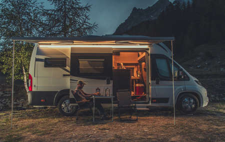 Caucasian Men in His 40s Working Online While on Vacation in Mountain Region. Remote Work on Laptop While Camping in a Wild. Camper Van as Mobile Office Theme. Standard-Bild