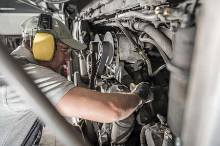 Forty Years Old Caucasian Automotive Technician Mechanic Looking Inside Vehicle Diesel Engine Compartment