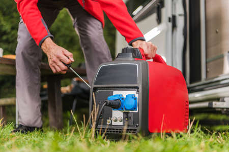 Caucasian Men in His 40s Firing Up Gas Powered Portable Inverter Generator To Connect Electricity To His Camper Van. Banque d'images