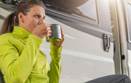Caucasian Woman in Her Late 30s Drinking Cup of Fresh Brewed Coffee in Front of Her Modern Camper Van While Camping in Wilderness