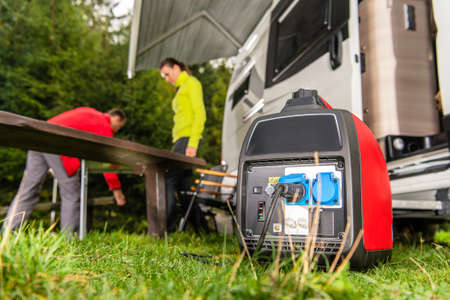Modern Gasoline Powered Generator Running Next to Camper Van Recreational Vehicle. Powering RV Camping Pitch with Own Energy Source. Banque d'images