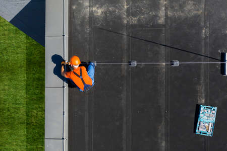 Caucasian Technician Wearing Orange Uniform and Hard Hat Installing Lightning Protection System Rod on Top of Commercial Building. Protect Structure From Elements. Imagens