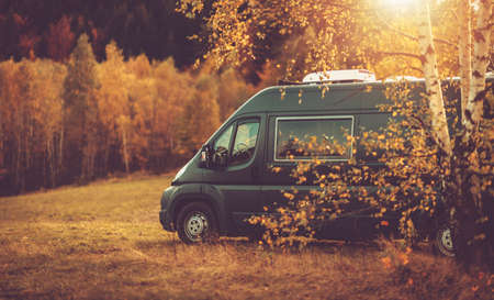 Autumn Fall Foliage RV Recreational Vehicle Camper Van Road Trip and Scenic Camping in Beautiful Place. Motorhome and the Scenic Nature. Travel Theme. Imagens