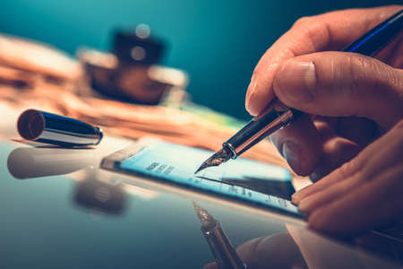 Caucasian Men Writing Pay Check Using Fountain Pen. Payment Preparing. Business Theme.