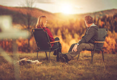 Caucasian Couple in Their 40s Seating in Front of Scenic Vista Enjoying Their Life and the Nature. Australian Silky Terrier Next to Chairs. Colorful Fall Foliage. Imagens