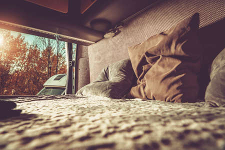 Camper Van Motorhome Comfortable Bed with Pillows and the Outdoor View. Rear Doors Opened. Fresh Air Coming Inside. RVing theme.