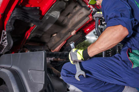 Caucasian Semi Trucks Mechanic with Large Wrench in His Hand Looking Inside Truck Vehicle Engine Compartment Looking For Potential Problems.