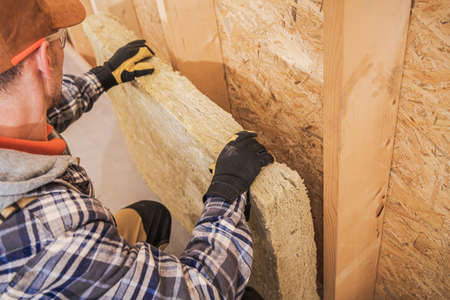 Caucasian Contractor Installing Mineral Wool Insulator Inside Wooden House Construction Wall. Construction Site Theme.