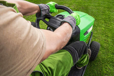 Caucasian Gardener on His Professional Grass Mowing Tractor Cutting Backyard Grass. Gardening and Landscaping Industry Theme. Imagens