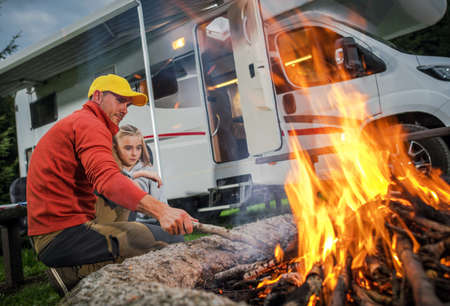 Recreational Vehicle RV Camper Camping and Family Time. Caucasian Father and His Daughter Hanging Next to Campfire on Their RV Park Pitch. Class C Motorhome in Background. Imagens