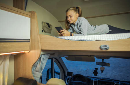 Caucasian Girl Hanging on Bunk Camper Bed with Her Smartphone During Camping Time and Rainy Weather. RV Travel Theme.