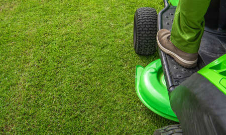 Pro Gardener and His Equipment. Professional Grass Mowing Tractor Mower in Action. Left Side Copy Space. Imagens