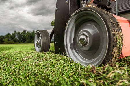Modern Gas Engine Grass Lawn Aerator in Action Close Up. Gardening and Landscaping Technologies Theme.