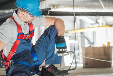 Caucasian Industrial Worker in His 40s Wearing Safety Harness. Warehouse HVAC Job. Imagens